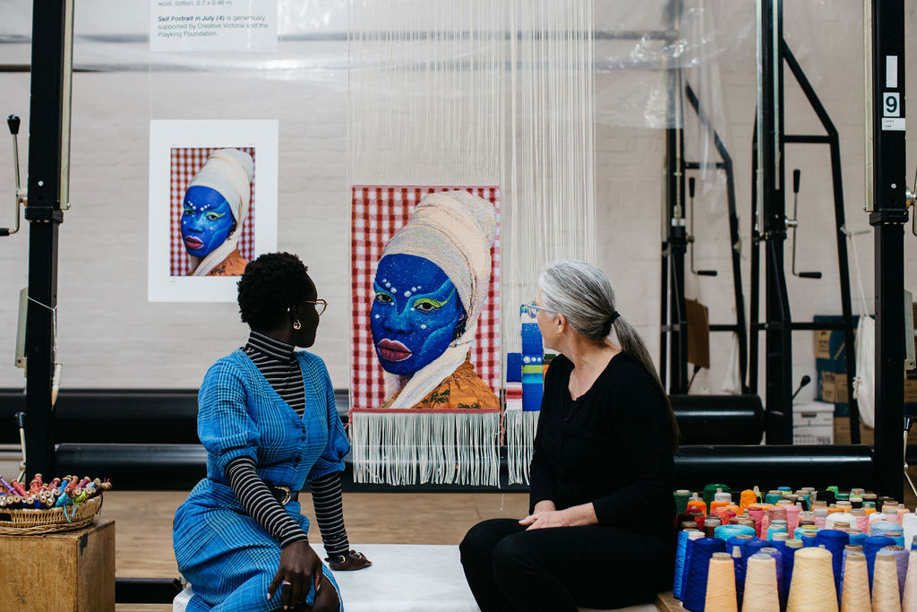 Atong Atem and Pamela Joyce in front of the 'Portrait in July (4)' tapestry, designed by Atong Atem in 2021. Photograph courtesy of Marie-Luise Skibbe.