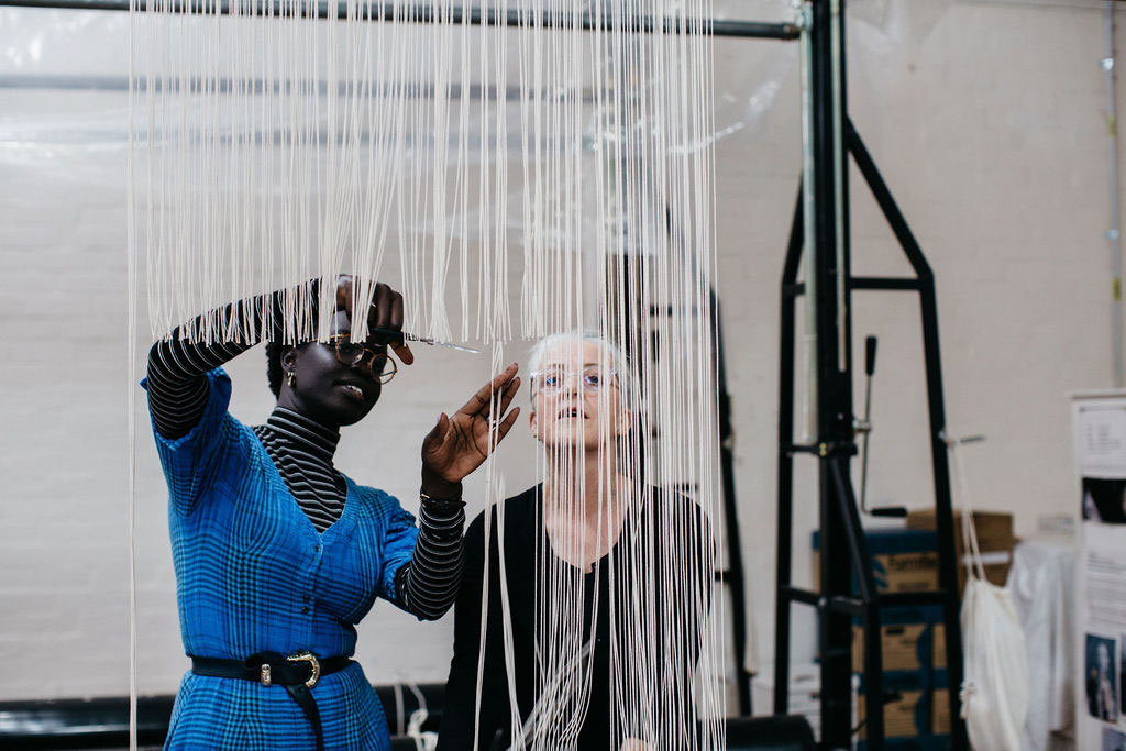 Atong Atem and Pamela Joyce cutting off the 'Portrait in July (4)' tapestry, designed by Atong Atem in 2021. Photograph courtesy of Marie-Luise Skibbe.