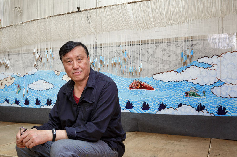 Guan Wei in front of 'Treasure Hunt' 2018, designed by Guan Wei and woven by Chris Cochius, Pamela Joyce, Jennifer Sharpe & Cheryl Thornton. Photo: Jeremy Weihrauch.